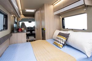 View of the bed and the interior in the Benivan 120 campervan