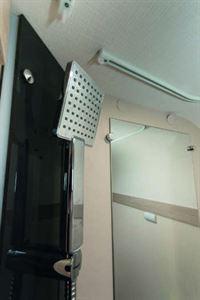 A big square, stylish shower head mounted on a smart black base.