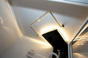 A hinged towel rail is mounted in the shower cubicle ceiling