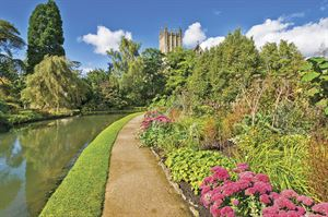 The Bishops Palace Gardens with Cathedral Tower and footpath in Somerset