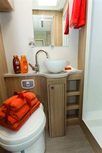 An ingeniously-designed cabinet-and-shelving srrrangement in the neat vanity area
