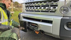A towhitch is fixed to one of the two mounting plates at the front of the Land Rover