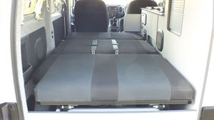 Seats folded down into a large double bed in the Small Campervan Nissan e-NV200