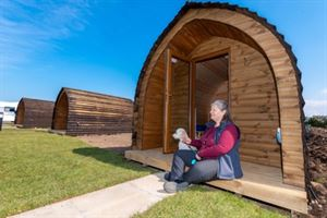 Pauline Gorley, general manager of Maryport Harbour and Marina with her poodle Milo outside one of the new camping pods