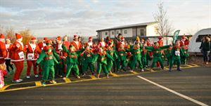 Children dressed as elves and parents dressed as Santa on the starting line at Love2Stay