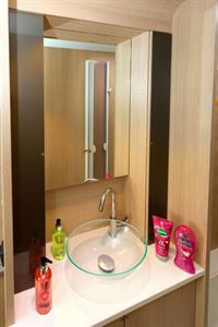Slim cabinets flank the mirror; the bowl has a pop-up plug