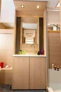 Slim shelved cabinets are on both sides of the mirror