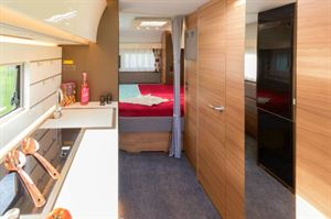 The bed is aligned transversely. a quality-fabric curtain partitions the bedroom from the rest of the caravan