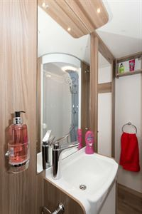 The washbasin is mounted on the forward side of the bedroom wall