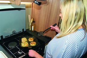 Monica cooking the fishcakes on a griddle pan