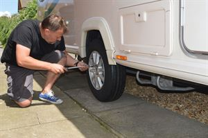 Undoing the wheel nuts on the caravan